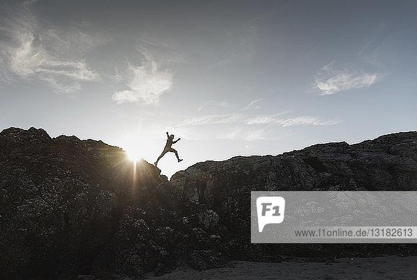 Frankreich  Bretagne  junger Mann springt bei Sonnenuntergang auf einen Felsen
