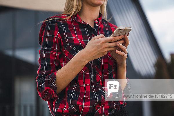 Frau mit kariertem Hemd mit Handy in der Hand  Teilansicht