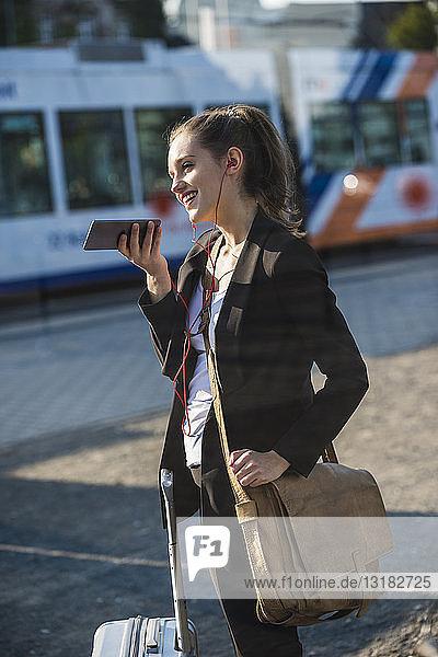 Lächelnde junge Frau mit Gepäck an der Straßenbahnhaltestelle in der Stadt per Handy