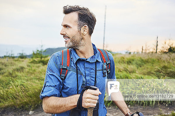 Smiling man hiking in the mountains turning round