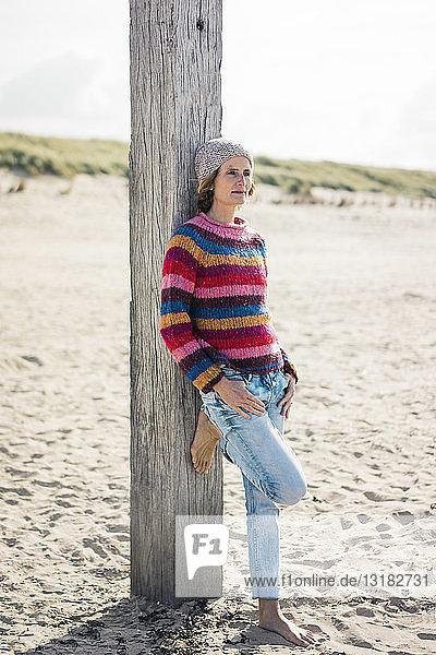 Reife Frau  die sich am Strand entspannt und sich auf eine Stange stützt