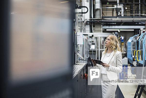 Frau mit Tablette an der Maschine in der Fabrikhalle  die sich umsieht