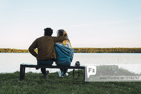 Young couple sitting on a bench  looking at the lake