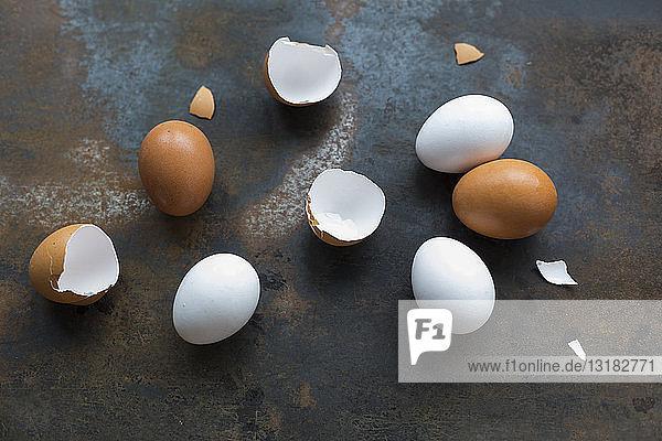 Weiße und braune Eier und Eierschalen auf rostigem Metall