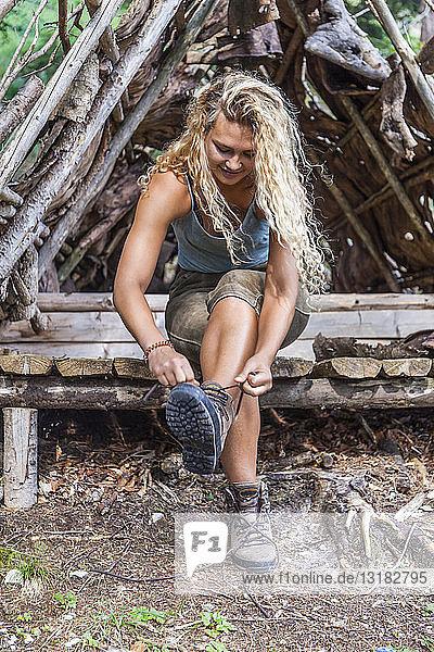 Junge Frau sitzt auf Bank und schnürt ihre Wanderstiefel