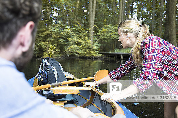 Young woman pulling canoe on a forest brook with man inside