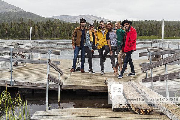 Finnland  Lappland  Porträt von Freunden  die auf einem Steg an einem See stehen