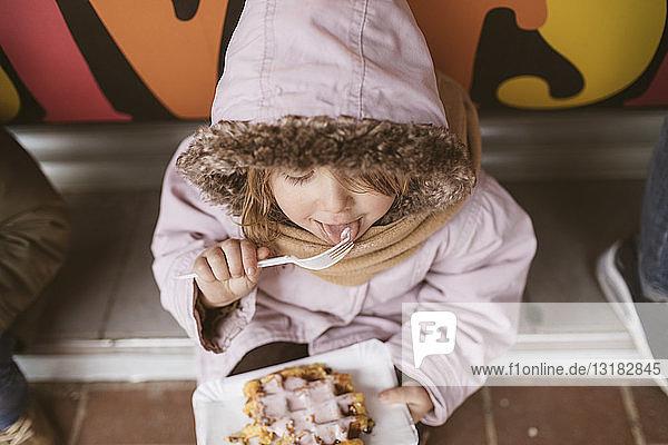 Belgien,  kleines Mädchen isst im Winter belgische Waffel im Freien, Belgien,  kleines Mädchen isst im Winter belgische Waffel im Freien
