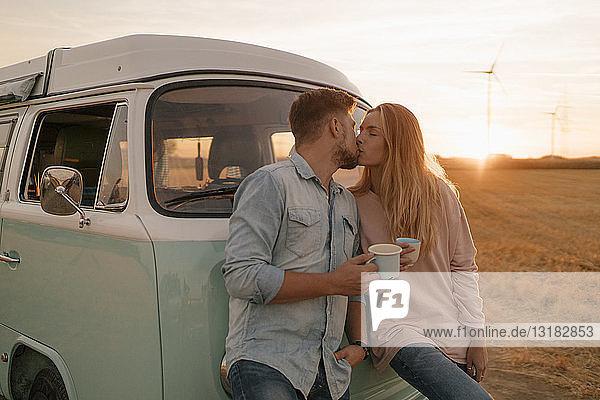 Junges Paar küsst sich am Wohnmobil in ländlicher Landschaft