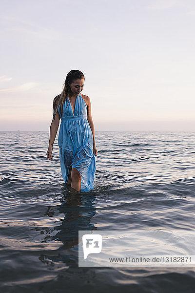 Junge Frau in blauem Kleid geht bei Sonnenuntergang im Wasser am Meeresufer spazieren
