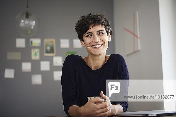 Porträt einer lächelnden Frau  die zu Hause am Tisch sitzt
