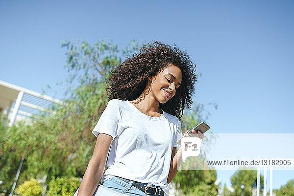 Lächelnde junge Frau schaut auf Handy