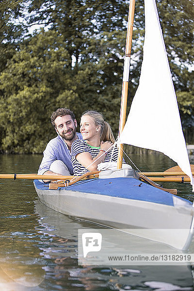Happy young couple enjoying a trip in a canoe with sail