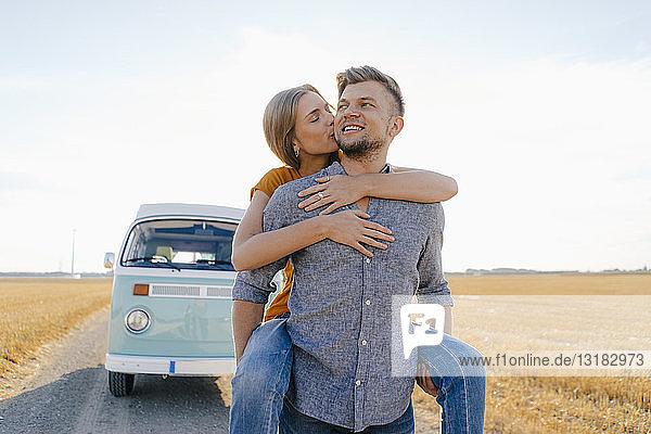 Glückliches Paar im Wohnmobil in ländlicher Landschaft