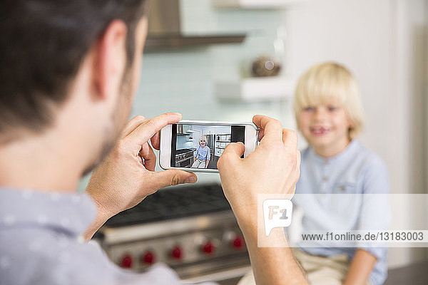 Father taking cell phone picture of son in kitchen