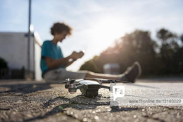 Boy landing his drone on the street