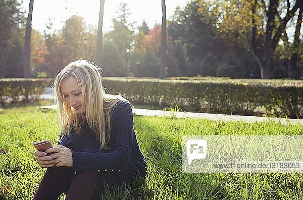 Lächelnde blonde Frau sitzt auf einer Wiese im herbstlichen Stadtpark und benutzt ihr Smartphone