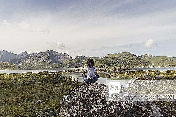 Junge Frau sitzt auf einem Felsen  schaut auf die Aussicht  meditiert  Lappland  Norwegen