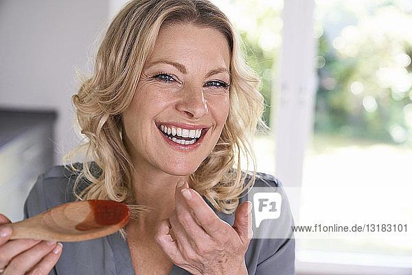 Porträt einer glücklichen Frau  die Tomatensauce vom Kochlöffel probiert