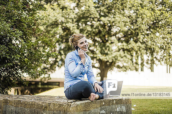 Smiling woman sitting in urban park talking on cell phone