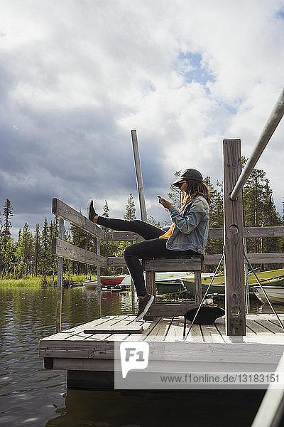 Finnland  Lappland  Frau sitzt auf einem Steg an einem See und benutzt ihr Handy