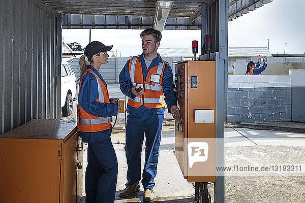 Zwei Arbeiter in Overalls und reflektierenden Jacken