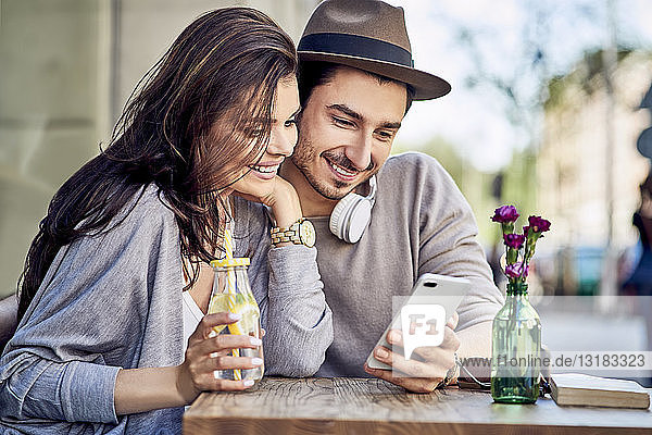 Happy young couple looking at cell phone at outdoors cafe