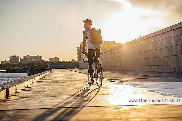 Junger Mann mit Rucksack auf dem Fahrrad auf der Uferpromenade am Flussufer bei Sonnenuntergang