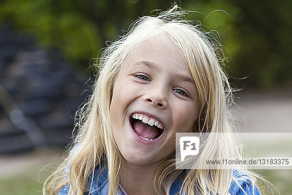 Portrait of laughing blond girl outdoors