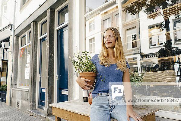 Niederlande  Maastricht  blonde junge Frau mit Blumentopf in der Stadt