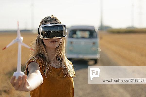 Junge Frau mit VR-Brille am Wohnmobil in ländlicher Landschaft hält Modell einer Windkraftanlage