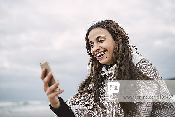 Portrait of laughing young woman looking at cell phone