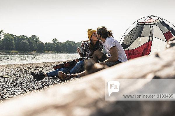 Junges Paar mit Gitarre küsst sich in einem Zelt am Flussufer