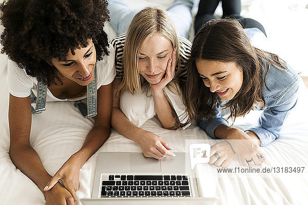 Three girlfriends lying on bed sharing laptop