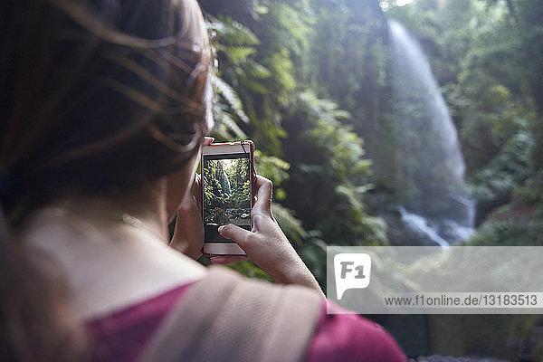 Spanien  Kanarische Inseln  La Palma  Frau beim Fotografieren eines Wasserfalls in einem Wald mit dem Handy