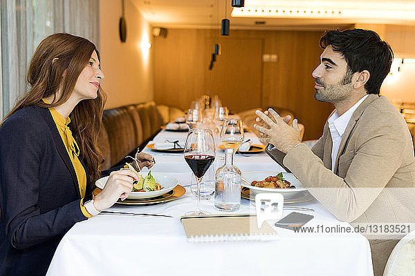 Smiling man and woman eating in a restaurant