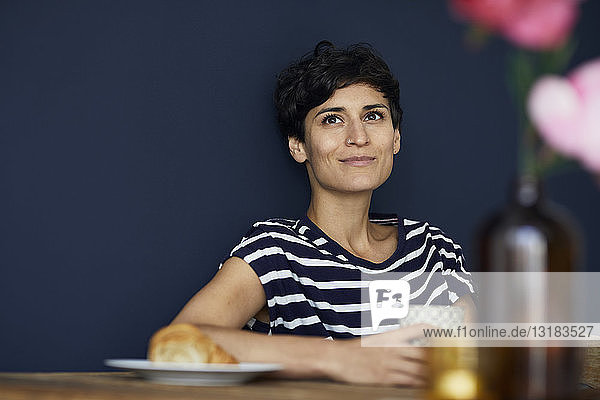 Portrait of smiling woman at home sitting at wooden table
