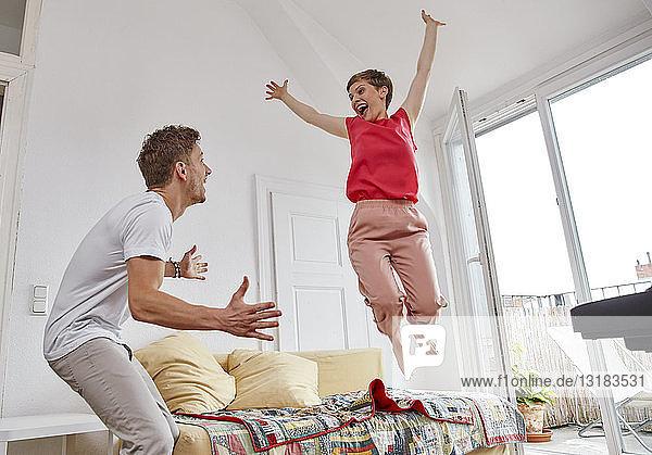 Aufgeregtes Paar im Wohnzimmer zu Hause
