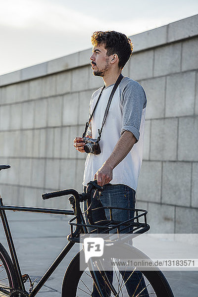 Young man with commuter fixie bike and camera looking around