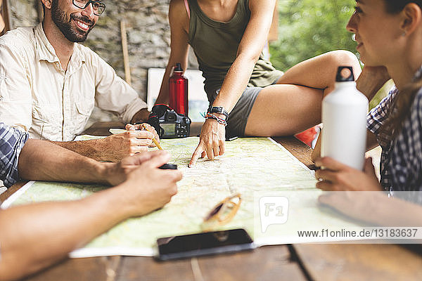 Group of hikers sitting together planning a hiking route looking at map