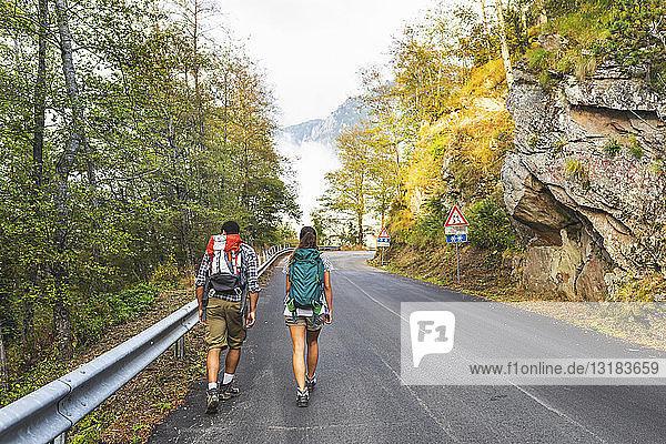 Italien  Massa  Rückansicht eines jungen Paares auf einer Asphaltstrasse in den Alpi Apuane