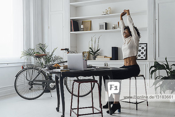 Mid adult woman sitting in her home office  smiling and stretching