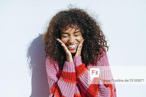 Porträt einer lachenden jungen Frau mit lockigem Haar vor weißer Wand