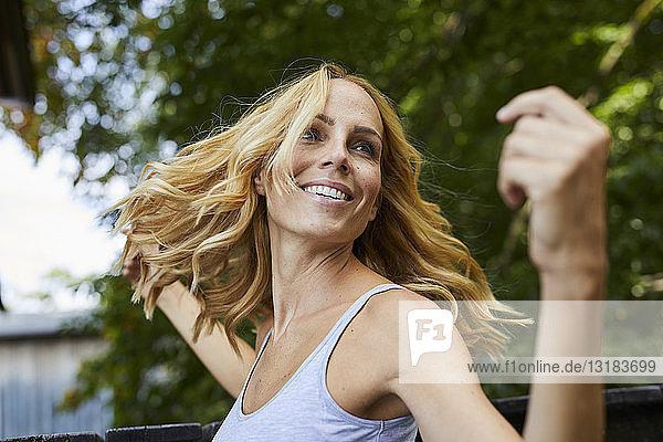 Unbeschwerte blonde Frau im Freien
