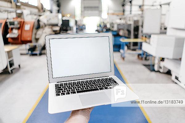 Handgehaltener Laptop mit leerem Bildschirm in einer Fabrikhalle