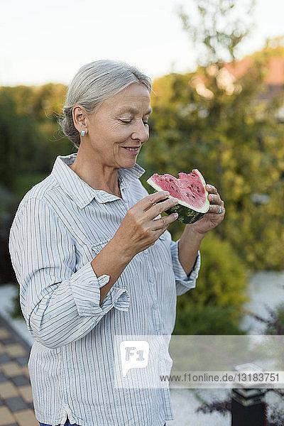 Senior woman eating watermelon slice in the garden