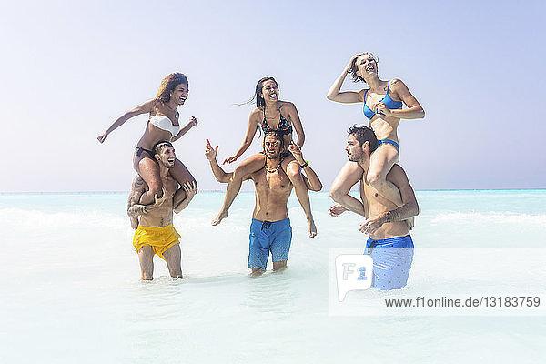 Freunde tragen ihre Freundinnen huckepack im Meer