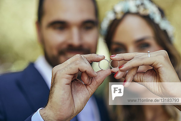 Happy bridal couple showing their wedding rings  close-up