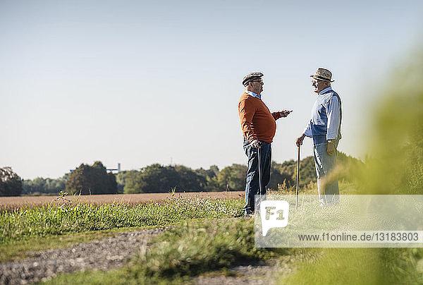 Zwei alte Freunde stehen auf den Feldern und reden über alte Zeiten