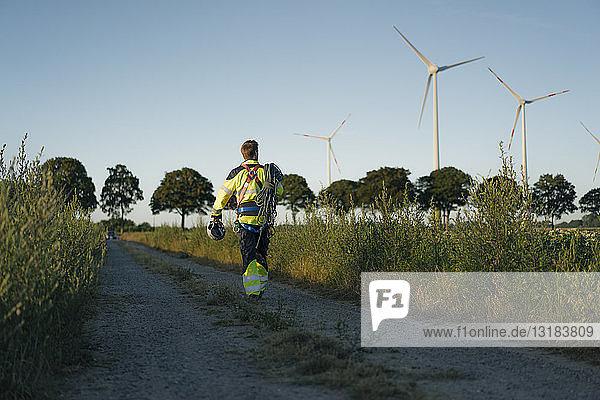 Techniker  der mit Kletterausrüstung einen Feldweg an einem Windpark begeht